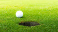 The ball at the hole on golf course Royalty Free Stock Photography