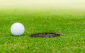 The ball at the hole on golf course Royalty Free Stock Images