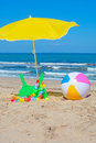 Ball and rackets green beach under a yellow parasol Royalty Free Stock Images