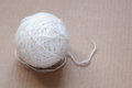 Ball of white wool yarn on cardboard background Royalty Free Stock Photo
