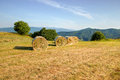 Balled packs of hay on morning meadow with valley Stock Photos