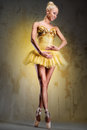 Ballerina beautiful in yellow tutu on point over obsolete wall Royalty Free Stock Image