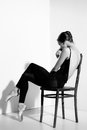Ballerina in black outfit posing on a wooden chair, studio background. Royalty Free Stock Photo
