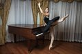Ballerina in black tutu standing on pointes at the grand piano Stock Photos