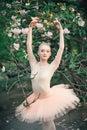 Ballerina dancing outdoors classic ballet poses in flowers lands