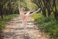 Ballerina dancing outdoors in green forest landscape at sunset