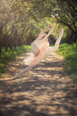 Ballerina dancing outdoors and jumping high into the air