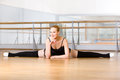 Ballerina does the splits sitting on floor in studio with barre and mirrors Stock Image