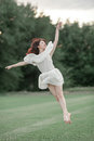 Ballerina jumps on lawn and trees background. Royalty Free Stock Photo