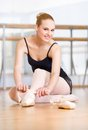 Ballerina laces the ribbons of the pointes sitting on floor Stock Photos