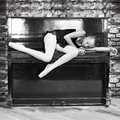 A ballerina and an old piano. . Music, dance, education.Black and white photo. Royalty Free Stock Photo