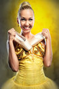 Ballerina smiling in yellow tutu holding pointe shoes Royalty Free Stock Photo
