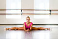 Ballerina split stretches in a full in a studio during warmup Stock Photography