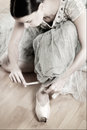 Ballerina tying pointe shoes her old worned before her rehearsal glimmer and soft focus desaturated colors with low contrast in Royalty Free Stock Image