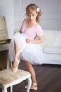 Ballerina tying pointe shoes in standing near the chair Royalty Free Stock Photography