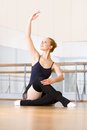 Ballerina works out sitting on the floor wooden in classroom with barre and mirrors Stock Images
