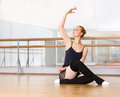 Ballerina works out sitting on the wooden floor in classroom with barre and mirrors Stock Photo