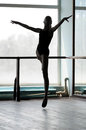 Ballet dancer in arabesque position silhouette of a ballerina making the air shot against the window with sunlight Stock Images