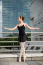Ballet dancer dancing on street ballerina with business buildings in background Royalty Free Stock Image