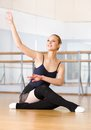 Ballet dancer does exercises sitting on the wooden floor works out in classroom with barre and mirrors Stock Photography