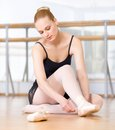 Ballet dancer laces the ribbons of the pointes sitting on wooden floor ballerina Royalty Free Stock Photography