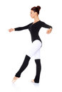 Ballet dancer practising her steps beautiful female in a black leotard and leggings and positions striking a graceful pose on a Royalty Free Stock Photo