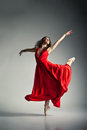 Ballet dancer wearing red dress over grey gorgeous young dark background Royalty Free Stock Photography