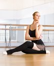 Ballet dancer works out sitting on the floor does exercises in classroom with barre and mirrors Stock Image