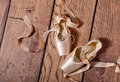 Ballet pointe shoes lie on wooden floor. Royalty Free Stock Photo