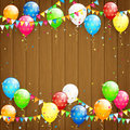 Balloons and confetti on brown wooden background Royalty Free Stock Photo
