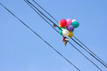 Balloons on electrical wires caught by above the street Royalty Free Stock Images