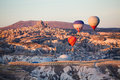 Balloons over uchisar castle in cappadocia at sunrise turkey Stock Photos