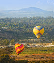 Balloons take flight del mar california two colorful hot air lift off over and the san dieguito river basin flying over the san Stock Photo