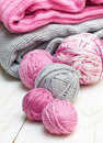 Balls of pink and gray yarn knitted fabric on a wooden background Stock Image