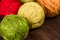 Balls of wool closeup many small rainbowcolors on the wooden table Royalty Free Stock Photos