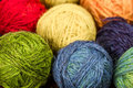 Balls of wool closeup many small rainbowcolors on the wooden table Royalty Free Stock Image