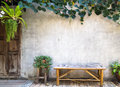 Bamboo bench with decorative plant on concrete wall background