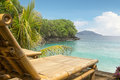 Bamboo chair on a beach small private overlooking blue ocean for summer holiday in tropical paradise Stock Photos