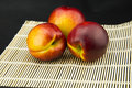 In the bamboo mat, three red nectarine Royalty Free Stock Photo