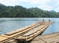 Bamboo raft floating in lake with mountain background Stock Images
