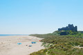 Bamburgh castle and beach on hazy summer day a Royalty Free Stock Images
