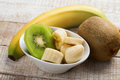 Banana and kiwi sliced in bowl on white wooden background selective focus Stock Photography