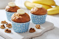 Banana muffins in blue paper cupcake case with nuts over wooden background Royalty Free Stock Photography