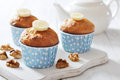 Banana muffins in blue paper cupcake case with nuts over wooden background Stock Images