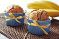 Banana muffins in ceramic baking mold with yellow ribbon over wooden background Stock Photos