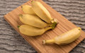Bananas bunch and a single babana on wooden pannel Stock Images