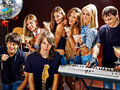 Band playing musical instrument group male and female performance in night club Stock Photography