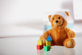 Bandaged Teddy Bear with Block Shapes on the Table Royalty Free Stock Photo