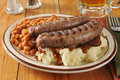 Bangers and mash with baked beans a plate of a mug of beer Royalty Free Stock Photos