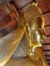 Bangkok, Thailand - January 1st 2020: Reclining Buddha statue gold face. Sleeping Buddha. Wat Pho, Bangkok, Thailand. Royalty Free Stock Photo